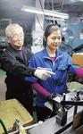 ベトナム人社員を指導する高齢社員
