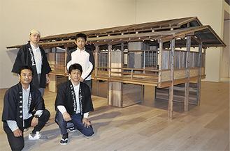 森美術館で組み立てた模型の前で。高木さん(前列左)と芹澤さん(同右) =4月13日撮影
