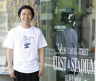 タケウチさんのイラストが描かれたTシャツを着る佐野店長