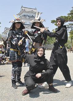 甲冑と忍者の衣装でポーズを決める留学生