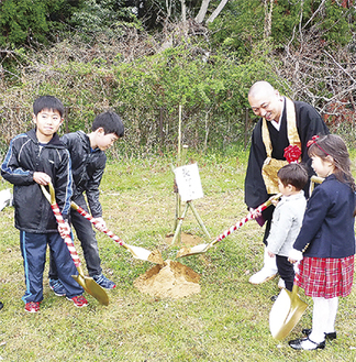 苗木の植樹を行う武内邦生住職と子どもたち=武内徳昭住職提供