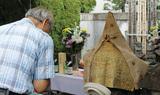 墓前で読経に合わせて手を合わせる参列者