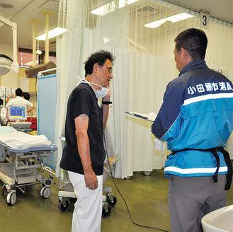 救急隊員から患者の様子を聞く清水智明医師=足柄上病院