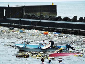 港湾内への流出物をボートなどに引き揚げる漁業関係者=29日朝、湯河原町福浦漁港