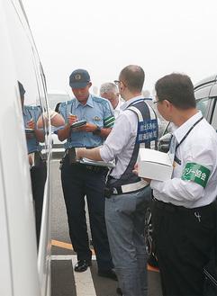 白タクと思わしき車両の運転手に質問する警察官ら