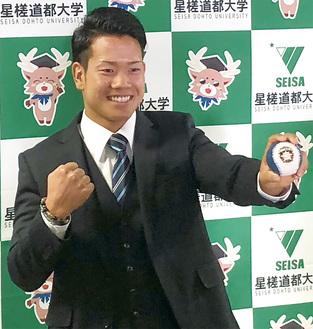 日本ハムのロゴ入りボールを手に笑顔の福田投手=星槎道都大提供