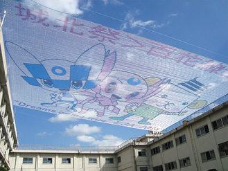 結束テープで作った3万個の輪をつないだ幅30mの巨大なモザイクアート