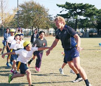 児童とタグラグビーを楽しむネド・ハニガン選手