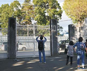 門を撮影する見学者ら