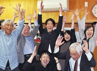 支援者らと万歳をする小谷氏(中央)