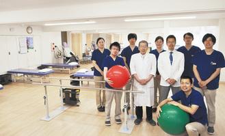 明るく広々としたリハビリ室で、竹田誠院長と崇朗副院長、理学療法士の皆さん