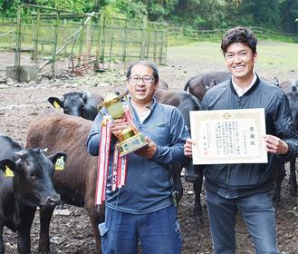 牧場で飼育している牛と長崎さん(左)と中川さん
