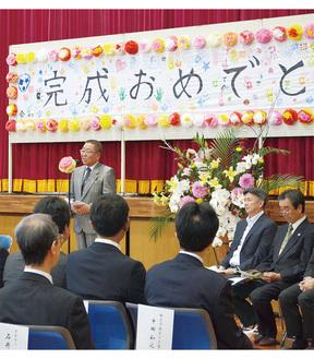 施設の子どもたち手作りの横断幕前であいさつする田崎吾郎理事長