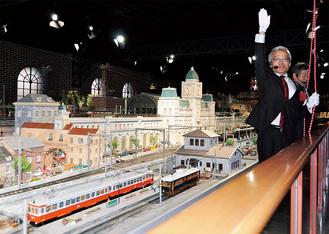 箱根登山鉄道の府川社長の合図で走り出す「103―107号」模型(左)。手前の黒い車両は、原信太郎氏制作の初代「チキ1形」模型