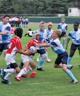 ボールを奪い合う小田原ラグビースクール(赤)とキングス・スクールの選手 =城山陸上競技場