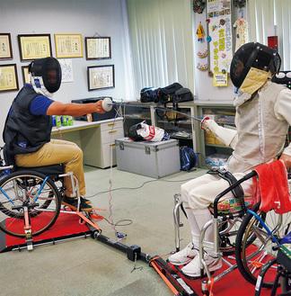 元車いすフェンシング選手の宮原紀彦さんと競技を体験する参加者
