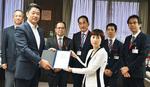 加藤市長に切手を贈呈するたなかさん(右)と郵便局長ら