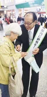 啓発物を配る小田原足柄納税貯蓄組合連合会の松谷会長