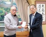 寄付金を渡す楽団の事務局長(左)