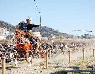 大観衆が見守る中、射手が疾走する馬の上から矢を放つ