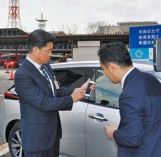 スマートフォンを操作して電気自動車のカギを開ける加藤市長