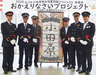折鶴アートを囲む5社の駅長・管区長と堀口さん(右)