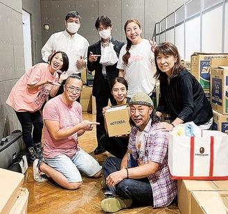 タオル入りの箱を手にする露木さん(中央)と、(株)門、ボランティアスタッフら