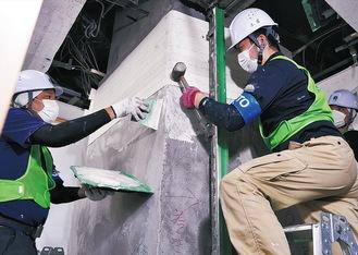 1階の柱に施工する様子。柱にベルトを巻き付け固定することから、包帯工法とも呼ばれている(10月6日撮影)
