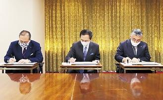 (左から)署名する守屋市長、黒岩知事、吉川理事長