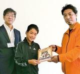 児童に自由帳を渡す石井委員長(右)