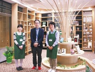 森の木々をイメージしたユニークな小田原関連書籍コーナーを紹介する青柳さん(中央)と同館スタッフ