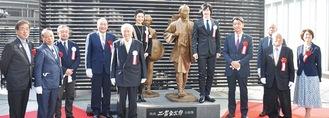 金次郎夫婦像の前に立つ高橋会長(手前中央)ら
