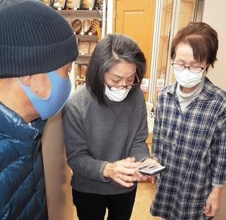 スマホで撮影した箱根駅伝の写真を見る3人