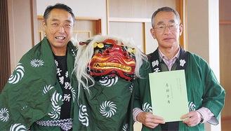 神尾さん(左)と、記念誌を紹介する二見会長