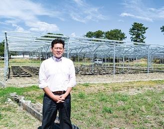 小山田氏とソーラーシェアリング設備。太陽光発電パネルの下では農作物が栽培される