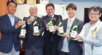「推譲」を手に笑顔を見せる小山田さん(中央)、井上さん(左から2人目)、加藤さん(左端)ら