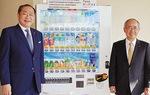 市役所に設置された自動販売機の前で、磯崎社長(右)と守屋市長