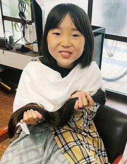 切った髪を手にする鈴木さん(家族提供)