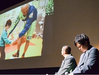 支援に尽力する久光重貴さんの記録映像を見つめる奥村監督(左)と涙をこらえる邦明さん