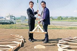 小田原市スポーツ課の職員にトンボを手渡す高木大輔会長(右)=報徳の森プロジェクト提供