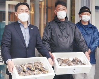 「鶴宝」を持つ松本町長(左)、皆木代表(中央)
