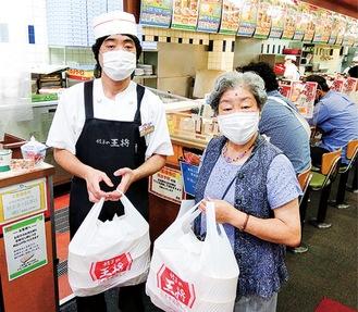 餃子の王将小田原店で弁当を受け取り、配布した鳥居会長(右)