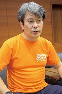 認知症サポーターのシンボルカラー・オレンジ色の同会のTシャツを着て、認知症について語る武井会長