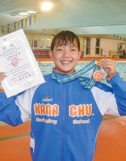 メダルと賞状を手に笑顔の久保田天来さん