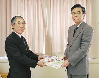 夏苅一壽大井町教育長(右)に啓発品を手渡す安藤会長(左)