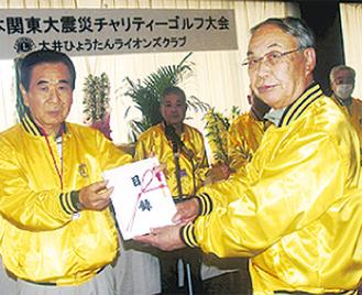 大会実行委員から義援金の目録を受け取る大澤会長(右)