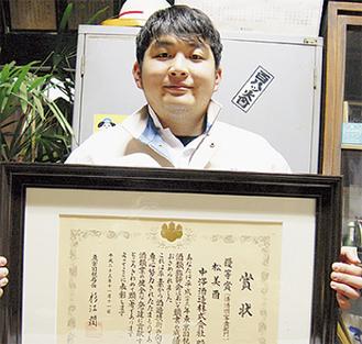 表彰状を手にする鍵和田亮さん