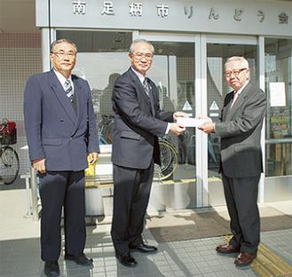 岸会長(右)に寄付金を渡す吉田社長(中)と遠藤支配人(左)