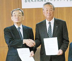 握手を交わす間宮町長と松丸理事長(左)