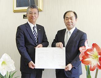 協定書を示す府川町長(左)と住澤社長
